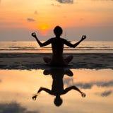 Mujer de la yoga que se sienta en actitud del loto foto de archivo