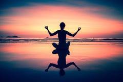 Mujer de la yoga que se sienta en costa de mar en la puesta del sol surrealista meditación Imágenes de archivo libres de regalías