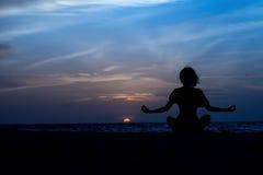 Mujer de la yoga que se sienta en el mar Foto de archivo