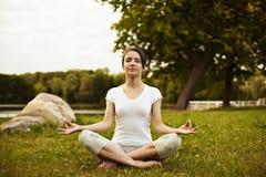 Mujer de la yoga que se sienta en la hierba en actitud del loto en parque Fotografía de archivo libre de regalías