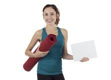 Mujer de la yogui con un tablero de anuncio en blanco Foto de archivo