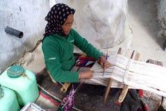 Mujer de Ladakhi que teje una alfombra Imágenes de archivo libres de regalías