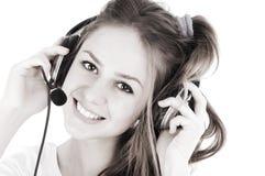 Mujer de las auriculares en el centro de atención telefónica que se coloca en la cartelera Foto de archivo libre de regalías