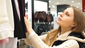 Mujer de las compras Comprador que mira la ropa adentro almacen de video