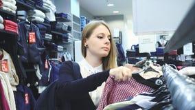 Mujer de las compras Comprador que mira la ropa adentro metrajes