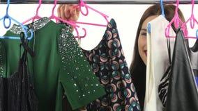 Mujer de las compras Comprador que mira la ropa en tienda de la ropa blanco almacen de metraje de vídeo