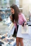 Mujer de las compras emocionada en una ventana de una zapatería foto de archivo