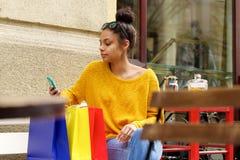 Mujer de las compras en el café usando el teléfono móvil Imagen de archivo libre de regalías