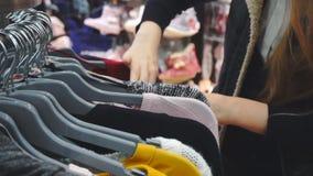 Mujer de las compras Manos del comprador que miran la ropa almacen de video