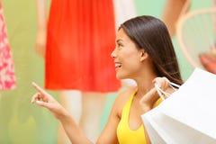 Mujer de las compras que mira la exhibición de la ventana de la ropa Imagen de archivo libre de regalías