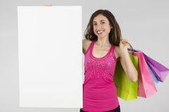 Mujer de las compras que muestra la bandera en blanco Fotografía de archivo libre de regalías