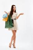Mujer de las compras que señala en el espacio en blanco Bolsos de compras Imágenes de archivo libres de regalías