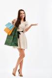 Mujer de las compras que señala en el espacio en blanco Bolsos de compras Foto de archivo libre de regalías