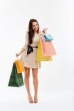 Mujer de las compras que señala en el espacio en blanco Bolsos de compras Fotos de archivo