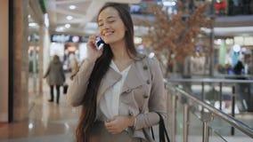 Mujer de las compras que sonríe con los bolsos que hablan en el teléfono en alameda Muchacha hermosa con smartphone en centro com metrajes