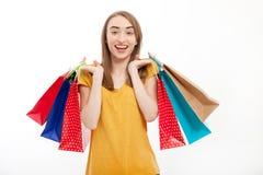 Mujer de las compras que sostiene bolsos coloridos y que sonríe en el fondo blanco con el espacio de la copia Foto de archivo libre de regalías