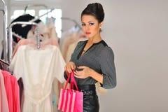 Mujer de las compras que sostiene el bolso en tienda al por menor Foto de archivo libre de regalías