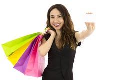 Mujer de las compras que sostiene una tarjeta de la muestra, foco en la tarjeta Foto de archivo