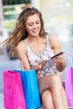 Mujer de las compras que usa la tableta digital Fotografía de archivo