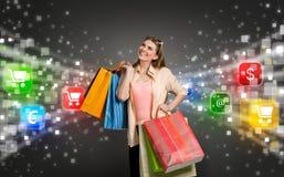 Mujer de las compras rodeada por los iconos del comercio electrónico Fotos de archivo libres de regalías