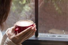 Mujer de las manos que sostienen la taza caliente de latte del café Imagenes de archivo