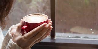 Mujer de las manos que sostienen la taza caliente de latte del café Imágenes de archivo libres de regalías