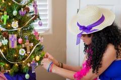 Mujer de Latina que adorna un árbol de Pascua Foto de archivo