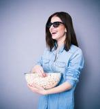 Mujer de Lauhging en los vidrios del cine que sostienen el cuenco con palomitas Foto de archivo