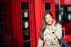 Mujer de Londres en el teléfono elegante por la cabina de teléfono roja Imagen de archivo