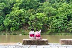 Mujer de los asiáticos que lleva el kimono japonés al lado de un río imagenes de archivo