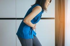 Mujer de los asiáticos que tiene el dolor de estómago y gastritis dolorosos, sufrimiento femenino del dolor abdominal, mano que e foto de archivo