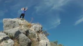 Mujer de los deportes que alcanza el top de una montaña metrajes