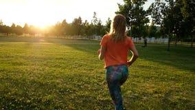 Mujer de los deportes que hace activar en la hierba en la puesta del sol en un parque de la ciudad, cámara lenta metrajes