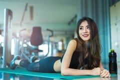 Mujer de los deportes que miente y que se relaja en la estera de la yoga en gimnasio de la aptitud con Imágenes de archivo libres de regalías