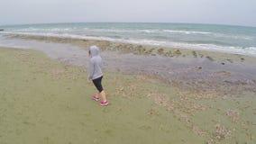 Mujer de los deportes que se mueve a lo largo de la playa y que disfruta del paisaje hermoso, tiro aéreo metrajes