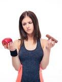 Mujer de los deportes que toma la decisión entre la manzana y el chocolate Fotografía de archivo libre de regalías