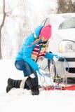 Mujer de los encadenamientos de nieve del neumático de coche del invierno Imagen de archivo