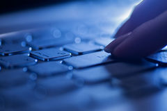 Mujer de los fingeres en un teclado del ordenador portátil Imagen de archivo