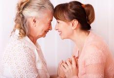 Mujer de los mayores con su cuidador en casa