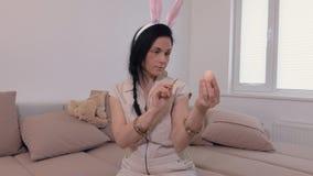 Mujer de los movimientos que piensa cómo huevo de Pascua de la pintura