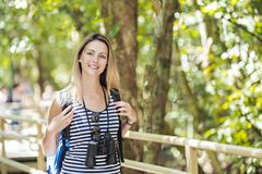 Mujer de los turistas con los prismáticos que buscan algo a lo largo del bosque foto de archivo