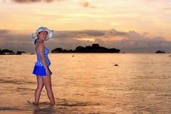 Mujer de los visitantes que mira la salida del sol sobre el mar Imagen de archivo