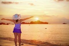 Mujer de los visitantes que mira la salida del sol sobre el mar Imagen de archivo libre de regalías