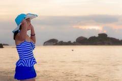 Mujer de los visitantes que mira la salida del sol sobre el mar Fotografía de archivo libre de regalías