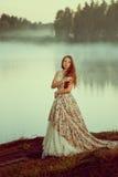 Mujer de lujo en un bosque en un vestido largo del vintage cerca del lago Foto de archivo libre de regalías