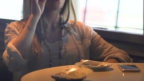 Mujer de lujo que se sienta en la tabla en café, teniendo bebida caliente, descanso para tomar café relajante almacen de metraje de vídeo