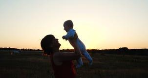 Mujer de mediana edad alegre que juega con su niño en un campo en la puesta del sol en el slo-MES metrajes