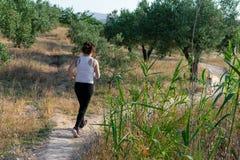 Mujer de mediana edad apta que corre a trav?s de un campo rural imagenes de archivo