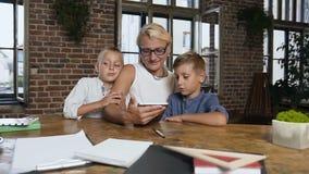 Mujer de mediana edad caucásica en los vidrios que hacen ejercicios con dos alumnos en la tableta, niños pequeños felices con apl almacen de video