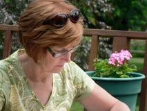 Mujer de mediana edad en jardín foto de archivo